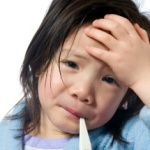 A young girl is sick and having her temperature taken.